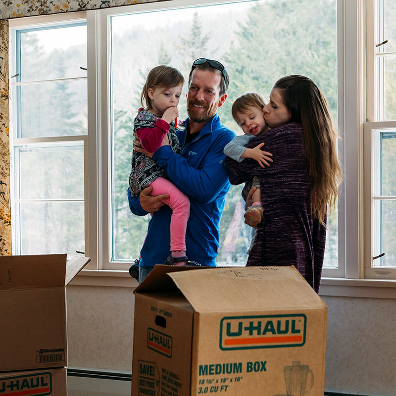 Family standing in new home after getting mortgage with Mascoma Bank
