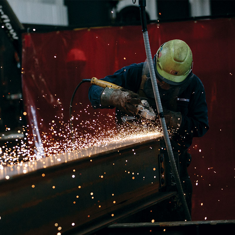 Steelworker at a local business grinding a weld on an steel beam
