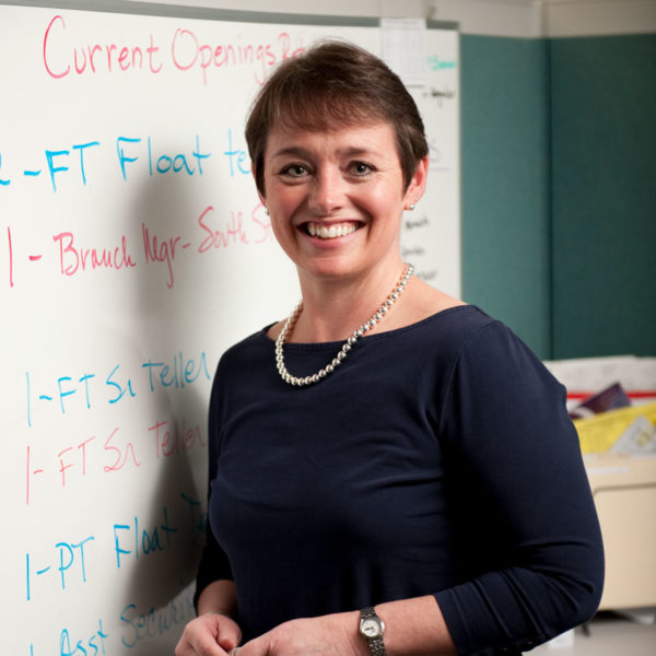 adult women standing in front of a white board smiling at the camera