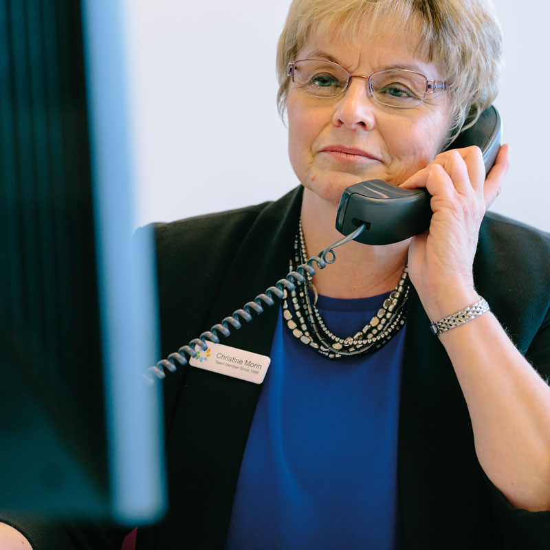 adult women working at Mascoma Bank listening on the phone