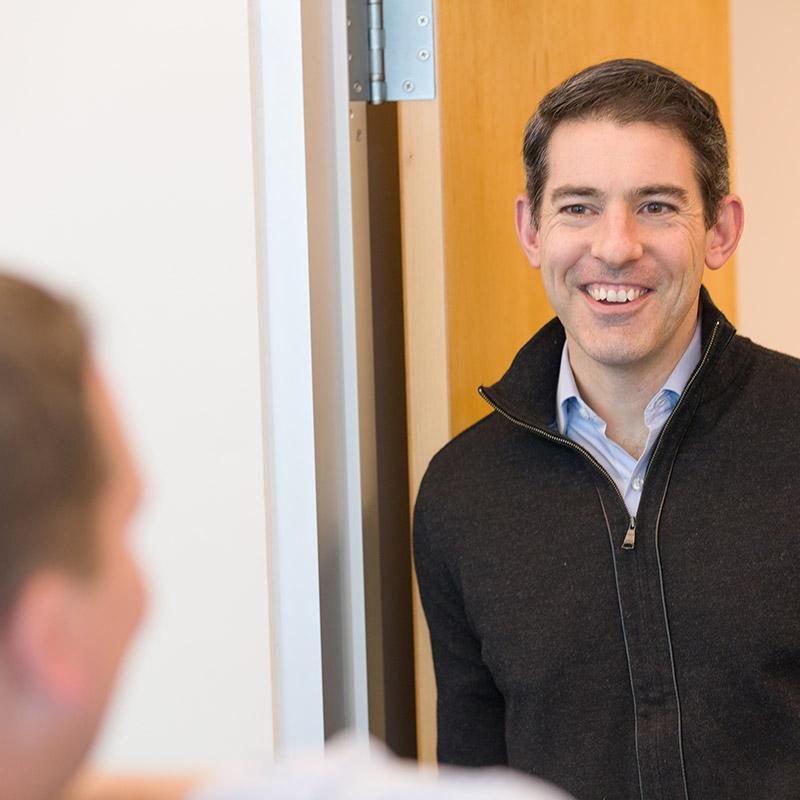 helpful bank employee wearing black pullover fleece leaning in a doorway smiling at customer