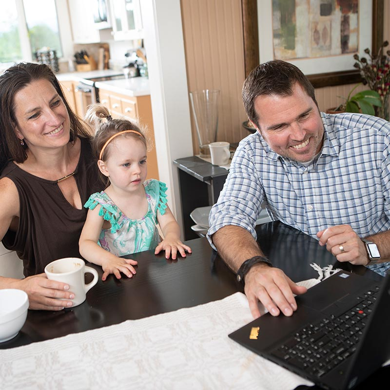 family of three sitting together at the dinner table looking at a computer screen