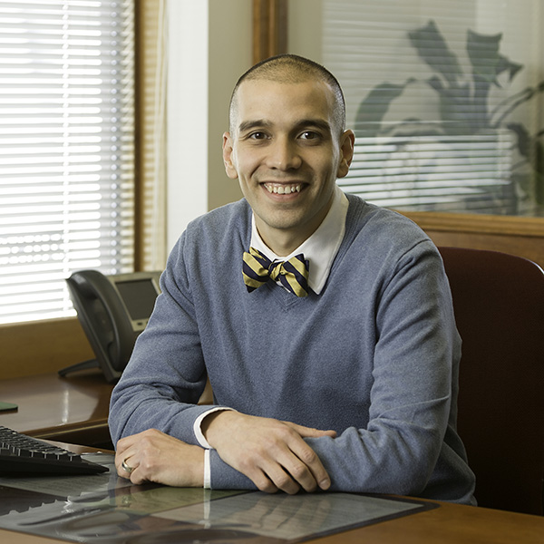 Smiling human resources employee wearing a blue sweater and gold and blue bowtie