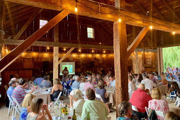 Interior of post and beam barn with people sitting at dinner tables