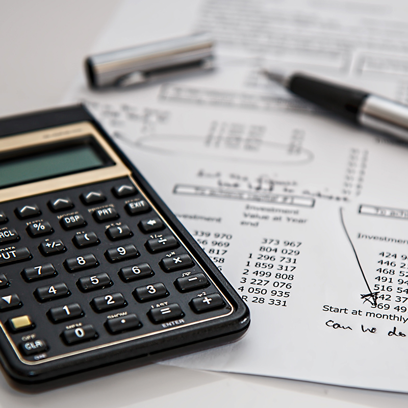 Black calculator next to a silver and black pen resting on a white paper with financial numbers showing