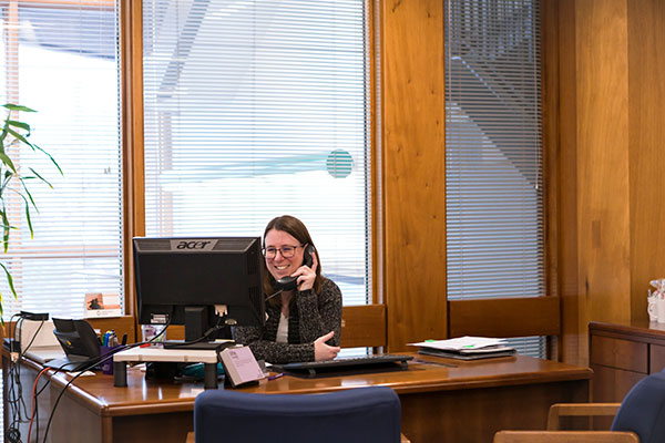 A woman behind a large desk in an office