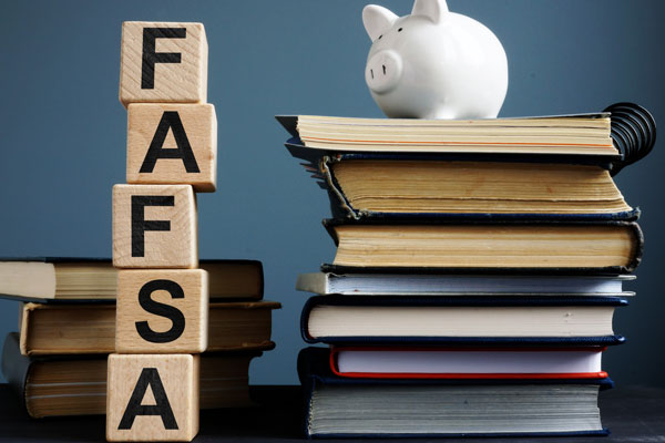 A piggy bank sitting on top of books with blocks that spell FAFSA