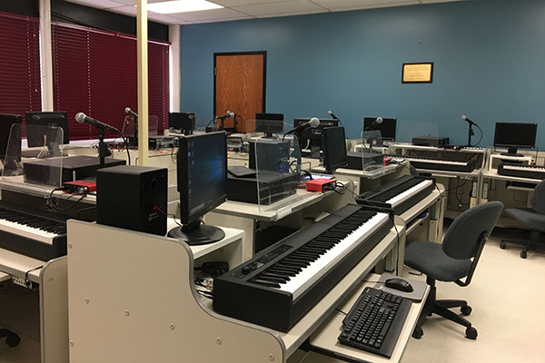 Music room with workstations containing a computer and musical keyboard