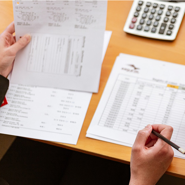 view of a desk with person's right hand holding a pencil and the left hand holding a financial document such as a bill or P&L sheet