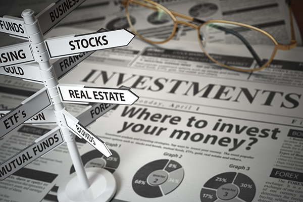sign posts on a newspaper pointing toward stock, mutual funds, real estate