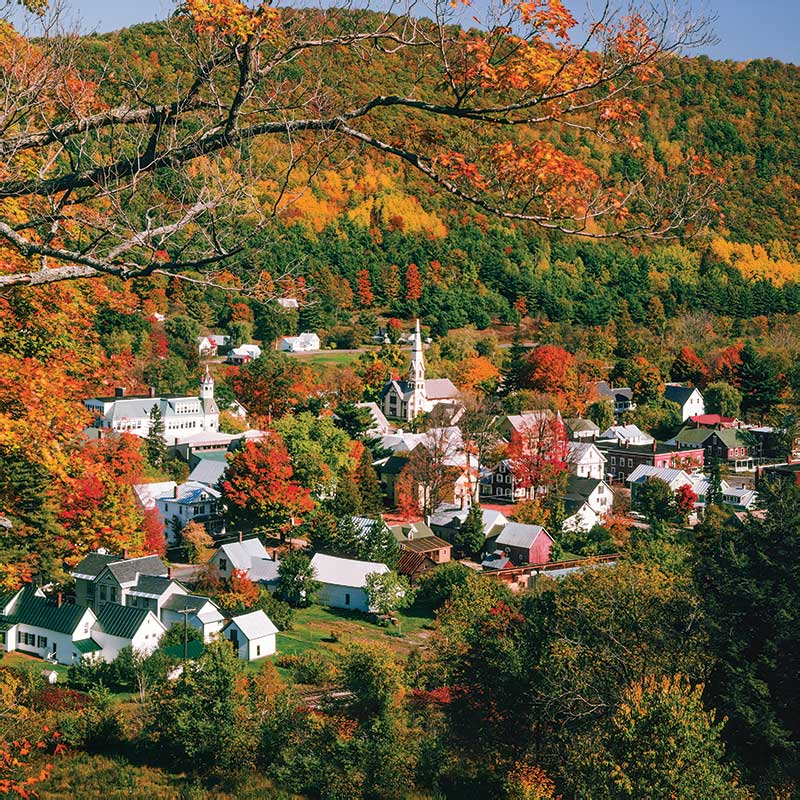 Country town at base of tree covered mountain with autumn colors