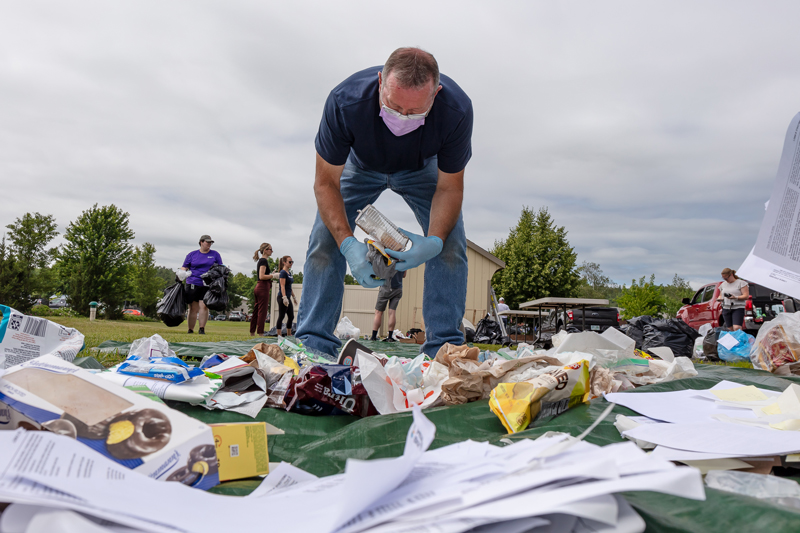 man bent over a pile of trash wearing a mask sorting it for recycling