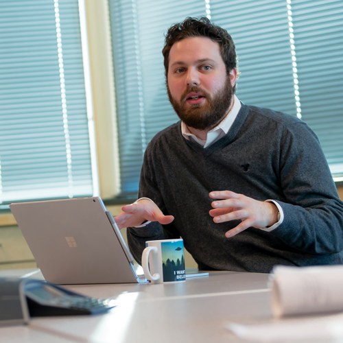 man with a beard talking with hand gestures in front of a laptop