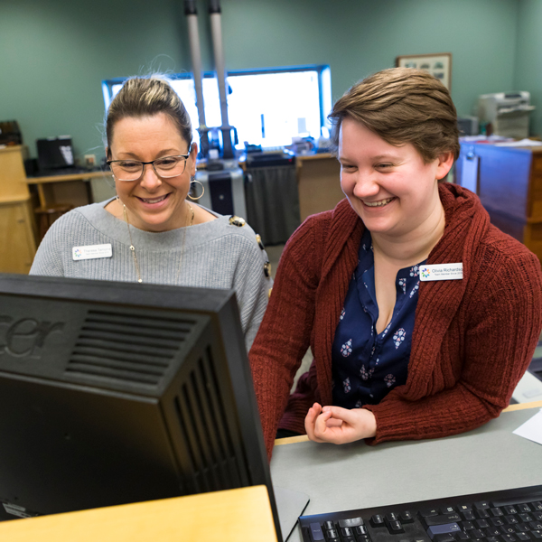 two bank employees laughing together at a computer monitor