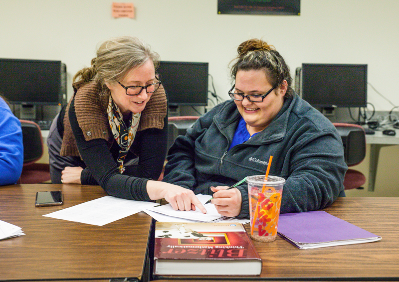 two women working together on school work smiling