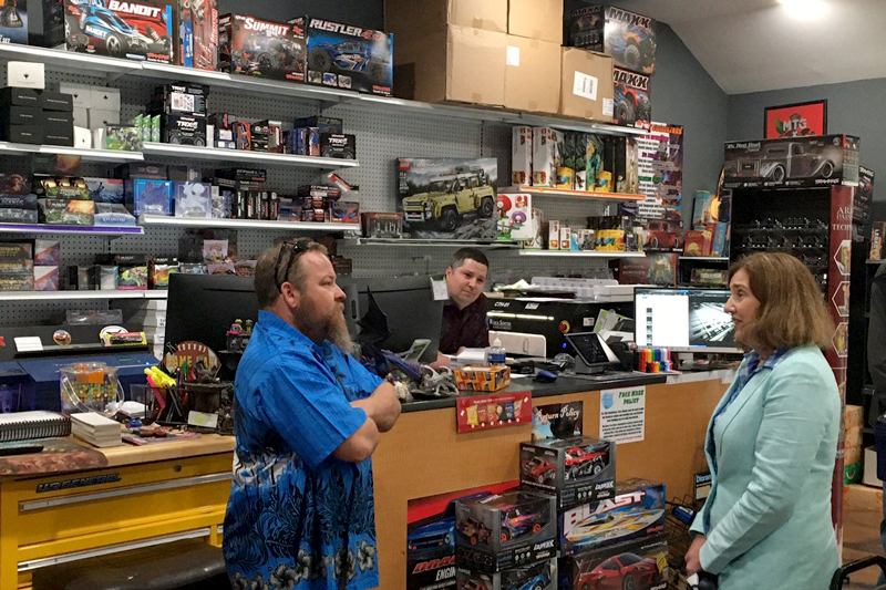 man and women talking inside a store with the store clerk behind the counter in the background